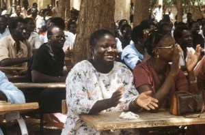Committees for Defense of Revolution meet August 1985 in Ouagadougou, Burkina Faso, above. After 1983 revolution working people, including women, built mass organizations to participate in running their country. Thomas Sankara speaks on International Women's Day, March 8, 1987, inset.