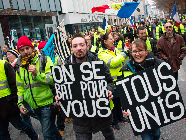 "Yellow vest protesters march in Rennes, France, Dec. 29. ""We fight for you,"" sign on left says. Protesters continue pressing for further concessions from the French government."
