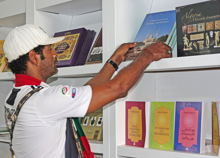 At Havana International Book Fair, where Algeria is country of honor, Oscar Creach Wenclar browses books at Algeria pavilion Feb. 11. He was proud that his father was one of nearly 700 Cuban volunteers who went to Algeria in 1963 to help defend the newly independent nation against imperialist-backed invasion by Moroccan troops