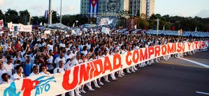 "Hundreds of thousands of people march during May Day rally in Havana to protest U.S. threats. Banner says, ""Unity, Commitment and Victory."""