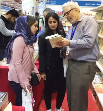 Above, Ögmundur Jónsson from U.K. talks at Pathfinder booth with Mohammed Ja'far, who is rebuilding library destroyed by Islamic State in village near Mosul. At left of photo is Pathfinder volunteer Martin Hill from U.K. Below, Steve Penner of Canada discusses Pathfinder titles with fair visitors.