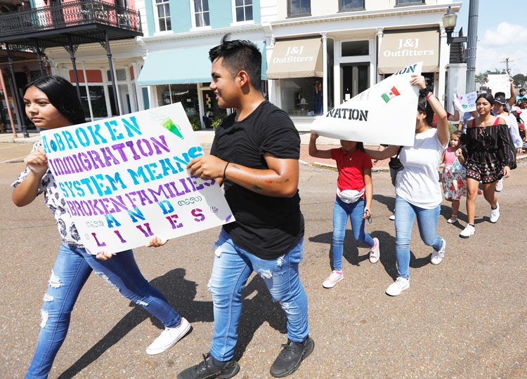 """We march so no other kid has to go through what we did,"" 18-year-old Dulce Basurto-Arce said at Aug. 11 protest in Canton, Mississippi. Some signs read, ""Our parents are not criminals."""