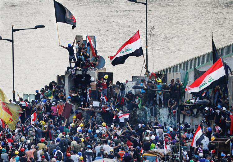 Manifestantes se congregan en el puente Al Jumhuriya en Bagdad el 29 de octubre, el quinto día de protestas contra injerencia iraní, corrupción del gobierno, y medidas antiobreras.