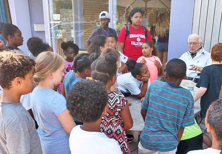 Allyn Gibson Sr. talking with children outside his Oberlin, Ohio, store. Appeal of court decision against Oberlin College officials deepens race-baiting smear campaign against Gibsons family.