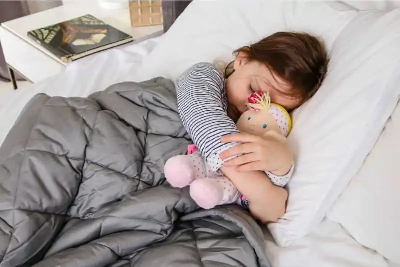 Child sleeping with lavender weighted blanket from