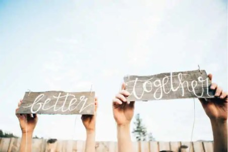 """couple arms and hands holding up sign that reads """"better together"""""""