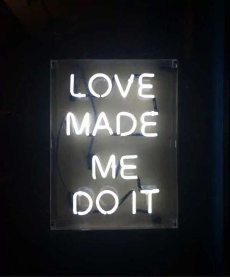 """Light up sign that reads """"Love made me do it."""""""