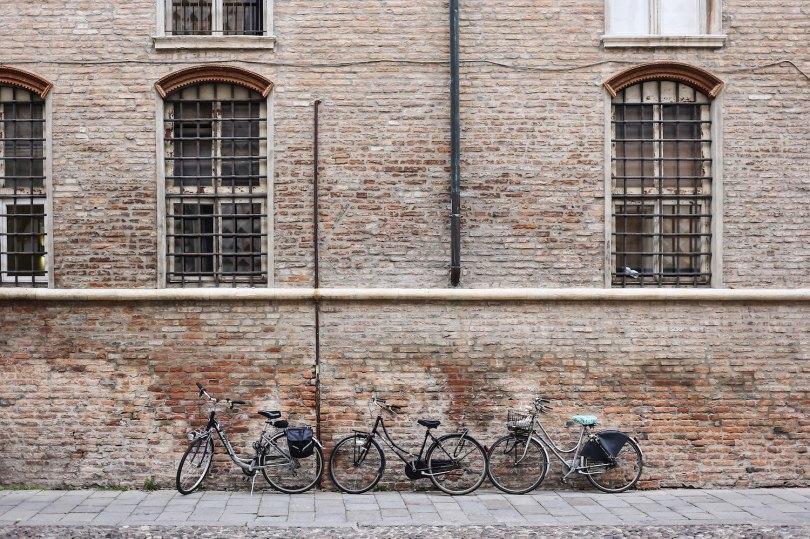 Una parete di un palazzo storico di Ferrara con le bici appoggiate