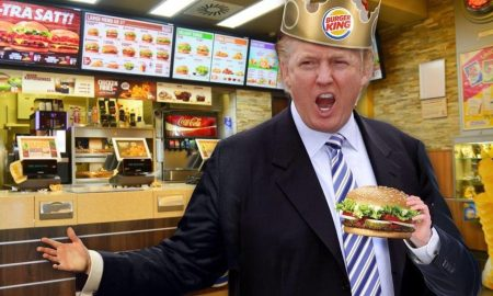 Trump holds up a big whopper, with his tiny hands, while wearing a Burger King crown.