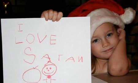 Little girl wearing Santa hat misspells Santa as Satan, holding up I love Satan letter instead.