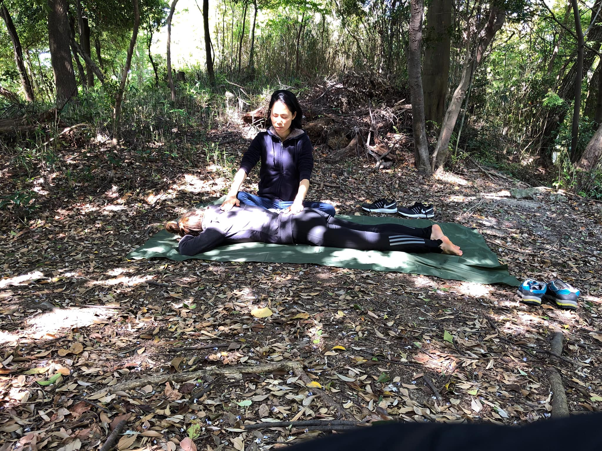 A woman offers energy healing and relaxation to Forest Bathing participant