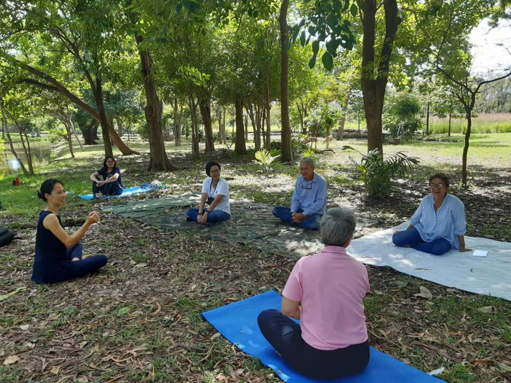 Shinrin Yoku training with a group of people sitting and learning in the forest