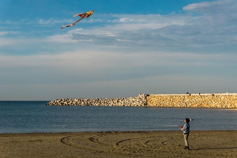 Niño volando una cometa en la playa