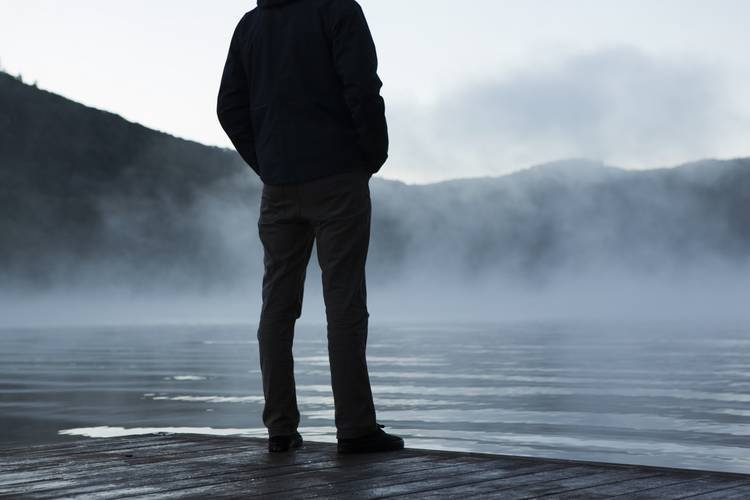 Hombre de pie solo en un muelle junto al agua brumosa - Poemas de Mike Larcombe