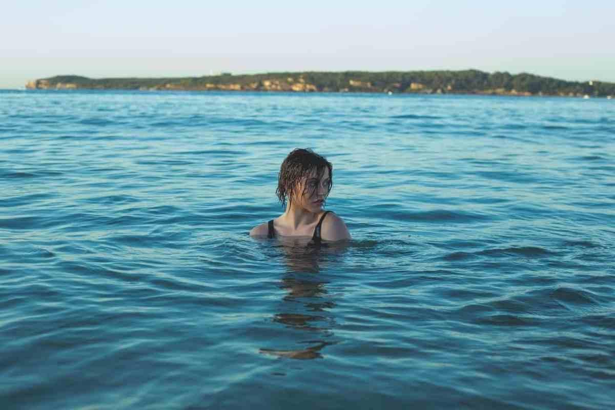 Mujer nadando en el lago con la cabeza fuera del agua - ¿No puede ver el bosque por los árboles?  Diseñando tu vida para volver a encarrilarte