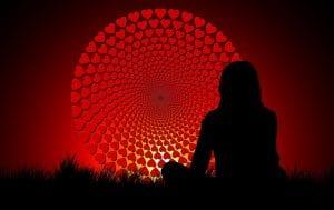 Mujer meditando delante de la rueda de corazones