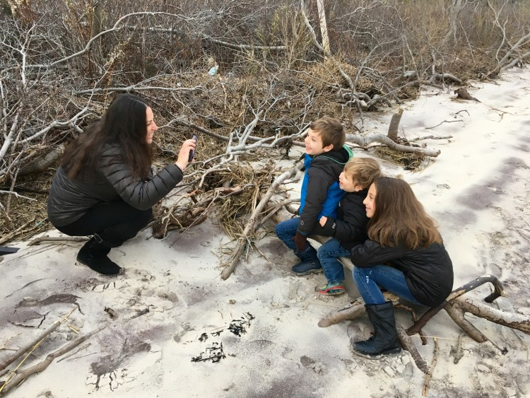 A picture of a mom taking a picture of her three kids sitting on a log at the beach in the winter.