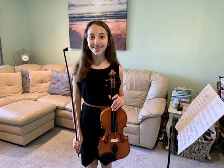 A 5th grade girl at her remote violin concert.