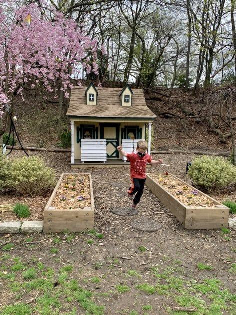 A little boy hopping on a playhouse porch at Centennial Park