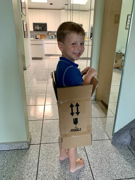 A little boy standing in a cardboard box