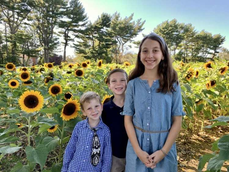 3 kids in front of sunflowers at Meyer Farm