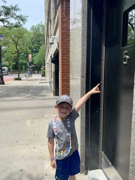 A little boy pointing to a five off of 5th Avenue in Manhattan