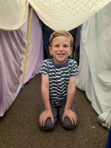 A happy little birthday boy in his birthday fort