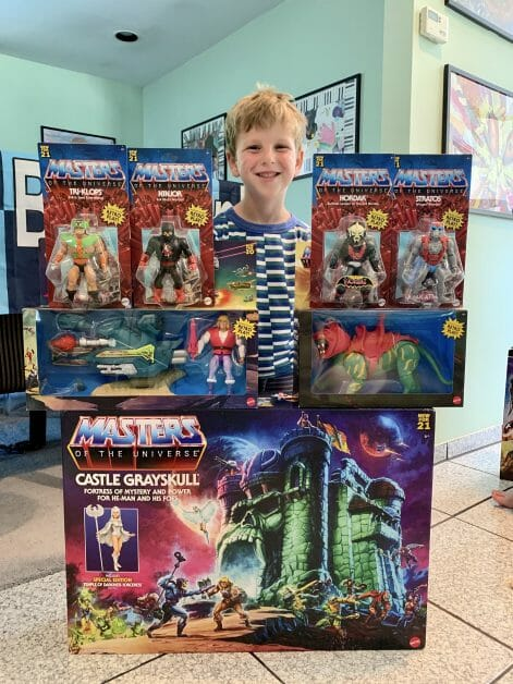 A little boy behind He-Man figures and the 2021 new Castle Grayskull