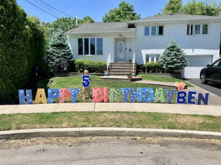 """A little boy holding up a 5 in a lawn """"happy birthday"""" sign"""