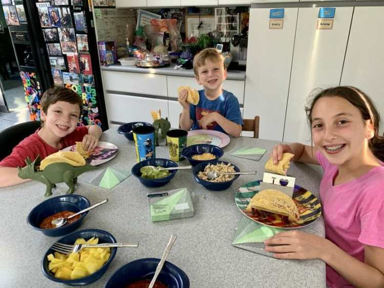 3 kids around a kitchen table eating Tacos on Taco Tuesday with Hudsonest napkins