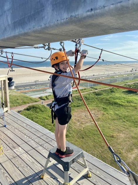A boy doing the zipline at Wild Play Jones beach. Zipline & Ropes Courses on Long Island.