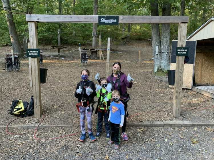 A mom & 3 kids at adventure park Long Island in climbing gear. Zipline & Ropes Courses on Long Island