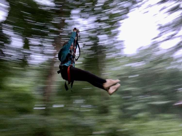 A girl zip lining through Adventure Park Long Island. Zipline & Ropes Courses on Long Island.