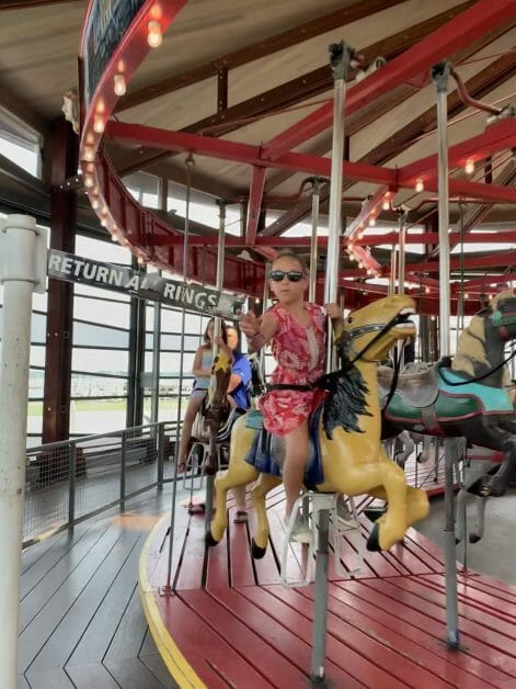 A little girl reaching for a brass ring on an antique carousel in Greenport