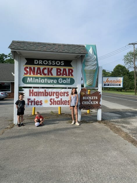 Three kids in front of the Drossos sign in Greenport