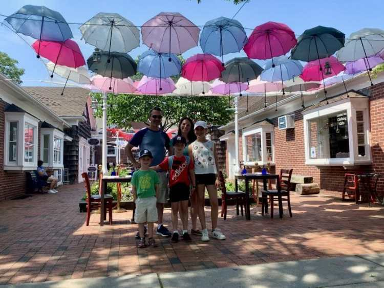 A family of five standing under umbrella decorations on Main Street in Greenport