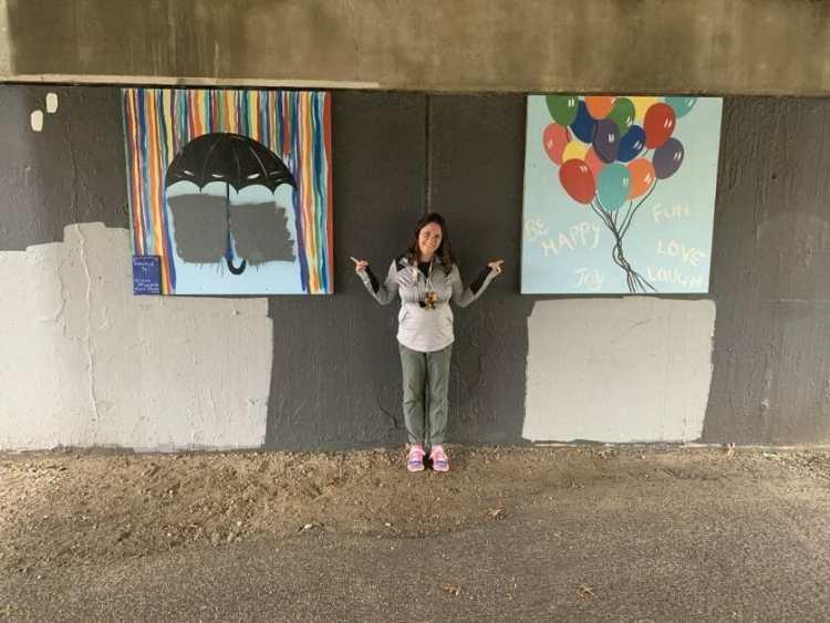 a woman in between 2 graffiti paintings at Massapequa Preserve