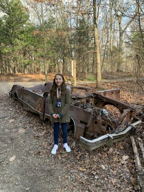 a girl in front of an abandoned car on a hike - Stillwell Woods Preserve