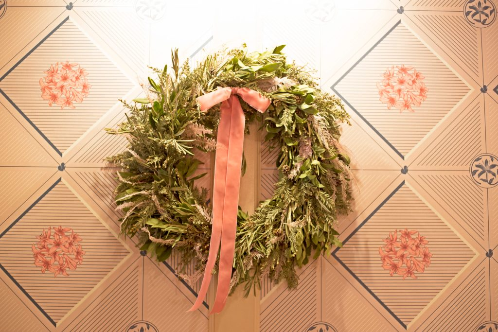 Wreathes hang adorably against the pink walls.