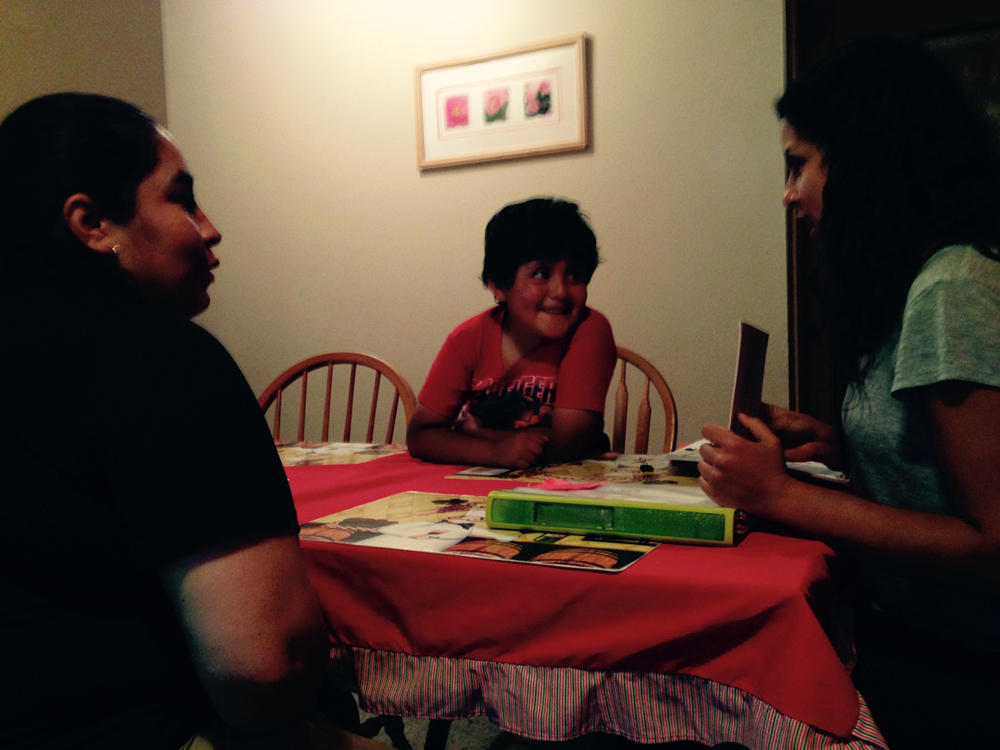 Maria Del Carmen Sanchez, her son Camilo Farfan and Teton Literacy Center early literacy coordinator Fiorella Lazarte working on reading skills at the family's apartment in Jackson.