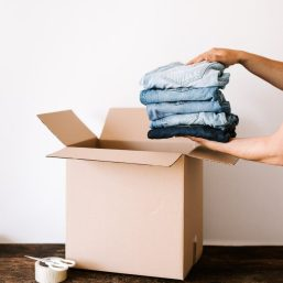 crop person packing jeans into carton container