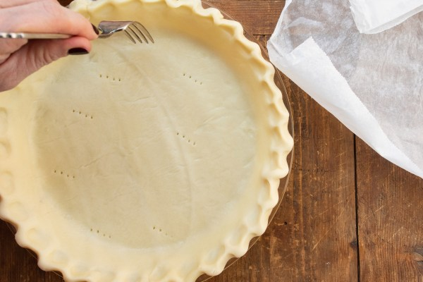 Pricking pie crust with a fork before blind baking