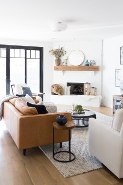 Tulsa-Remodel-Reveal-Modern-White-Farmhouse-black-windows-and-doors-modern-leather-sofa-article-sven-sofa-white-brick-fireplace-wood-beam-mantle-tv-gallery-wall-1