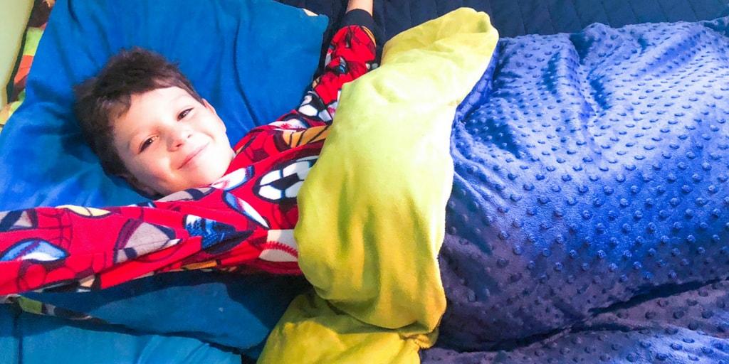 boy in bed under weighted blanket