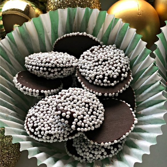 Nonpareil Candies sprinkled in white in a paper candy cup