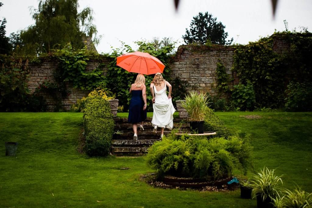Bride with bridesmaid under umbrella in garden