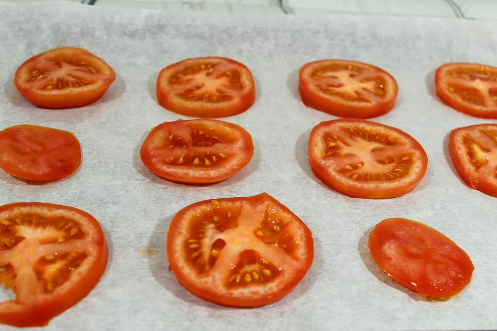 Tomato slices drizzled with olive oil for Keto Friendly Italian Tomato Pizza Bites