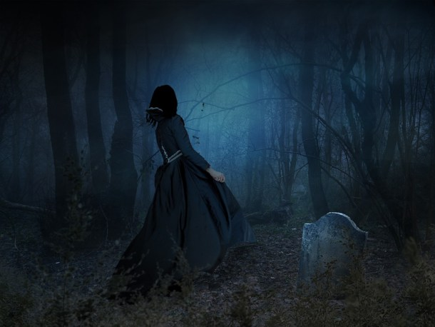 scary woman with bonnet in graveyard