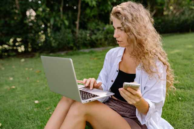 thoughtful female freelancer with smartphone surfing internet on laptop in park