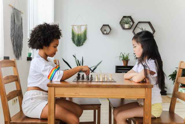 multiethnic thoughtful girls playing chess in modern room